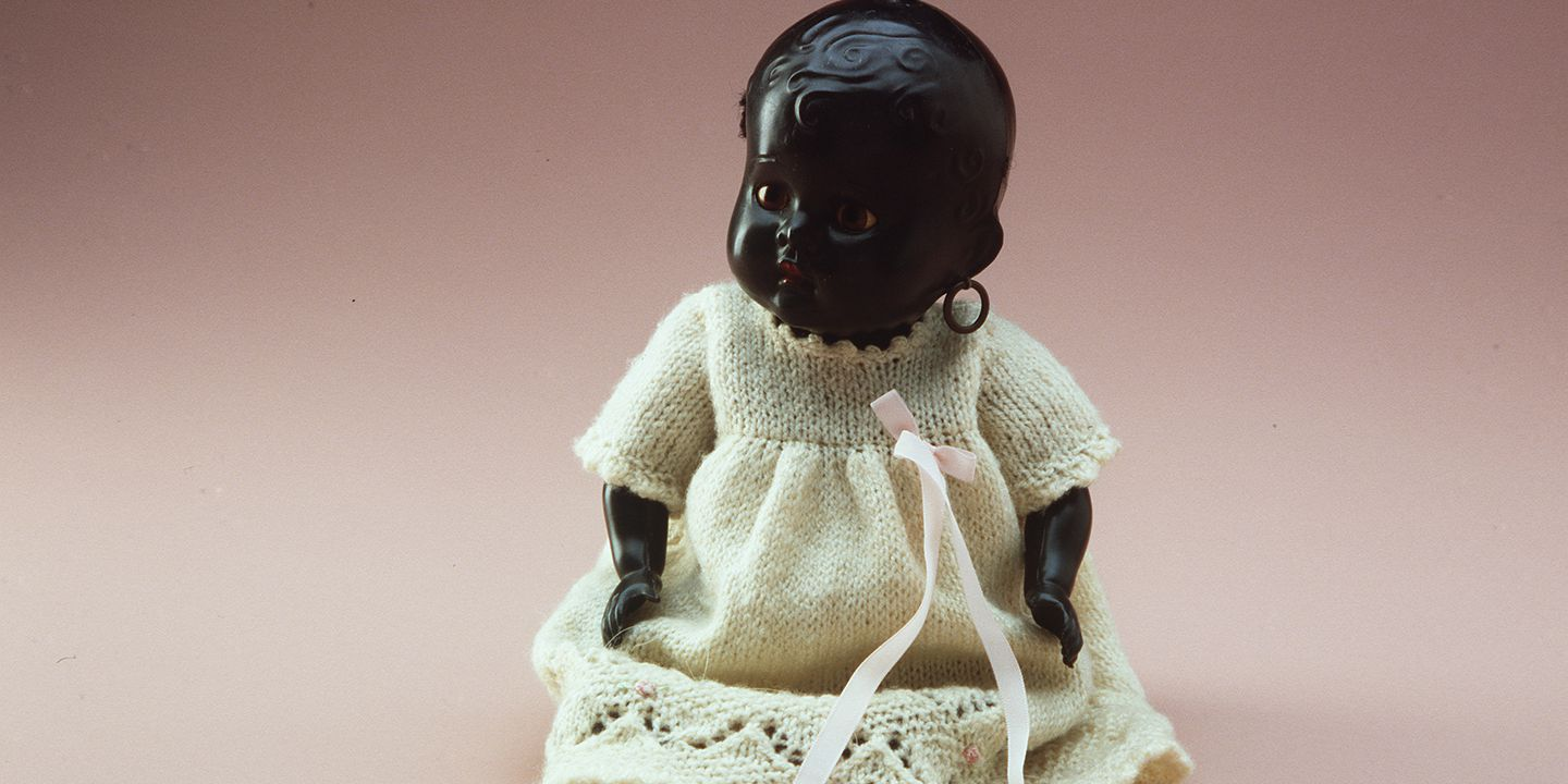 A10222 Doll, baby, plastic, black, head, arms and legs articulated at torso by means of an elastic band, hand knitted woollen dress and knickers, doll made by Cherub, Australia, early 20th century, clothes made by Beulah Brusetti (OF).. Click to enlarge.