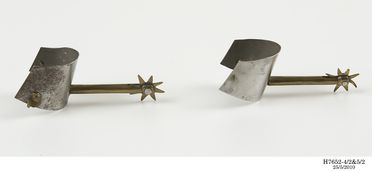 H7652-4 Miniature spur and ankle armour for left foot, part of miniature knight and horse, brass / steel, Paul Hardy, England, c 1890