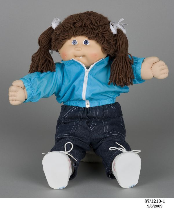 87/1210 Doll and accessories, 'Cabbage Patch Kid', plastic / textile / paper, Toltoys, China, c. 1986. Click to enlarge.