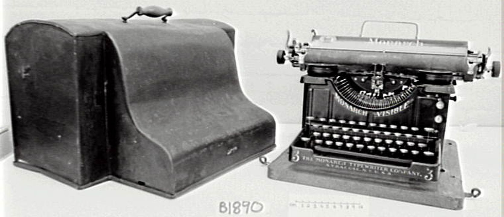 B1890 Typewriter 'Monarch Visible' made by [3] The Monarch Visible Co., Syracuse N.Y., U.S.A. no. 21134. In carrying case. 14 1/2' carriage (SB). ... in metal carrying case ... (LC).. Click to enlarge.