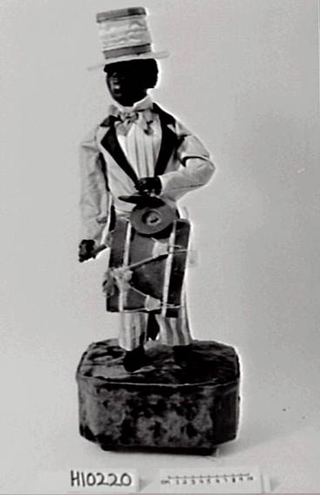 H10220 Musical automaton, African minstrel, papier mache / wood / metal / fabric / animal skin / glass / paper, made by Decamps, France, c. 1865-1920. Click to enlarge.