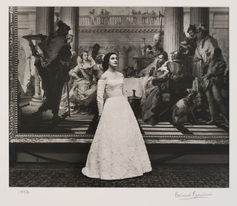 2009/43/1-1/2 Photographic print, black and white, model Catherine Patchell (nee Perkins) wearing Henry Haskin Gown of the Year, photographed in front of the 'Banquet of Cleopatra' painting in the National Gallery of Victoria, photograph by Bruno Benini, Melbourne, Victoria, Australia, 1956. Click to enlarge.