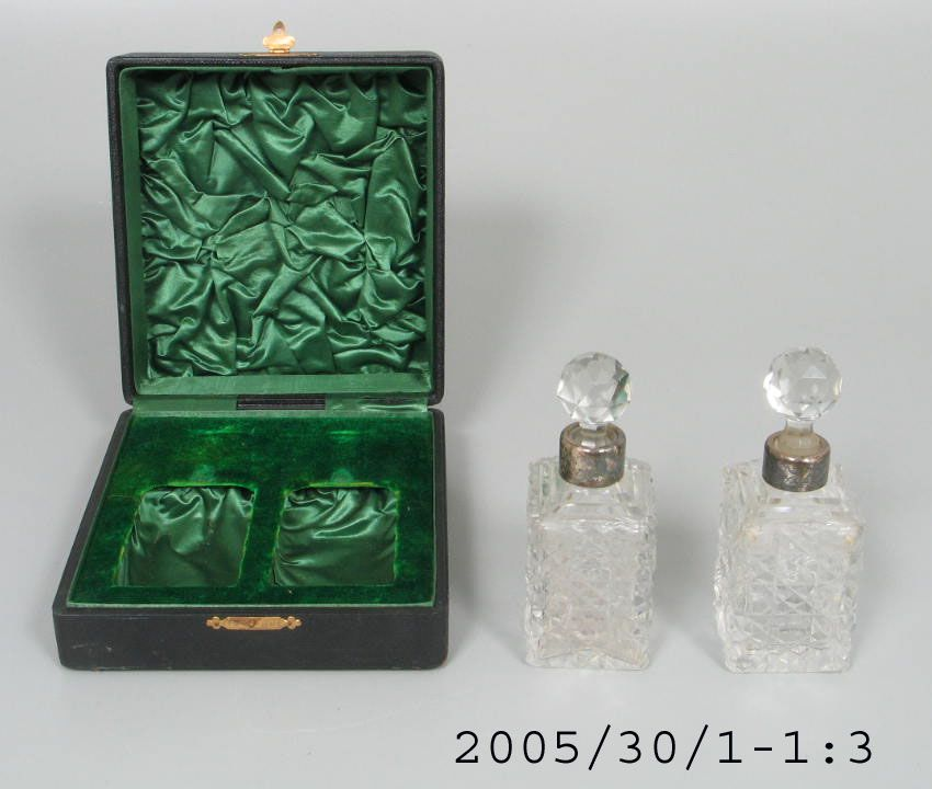 2005/30/1 Perfume bottles with stoppers (2), in case, crystal / silver / silk / velvet / leather, maker unknown, England / Australia, c. 1900. Click to enlarge.