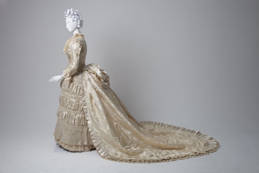2015/29/1 Wedding ensemble, consisting of bodice, skirt, train and cape, womens, silk / satin / lace / cotton / wool, made by Farmer & Co, Sydney, New South Wales, Australia, c. 1885. Click to enlarge.