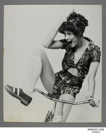 2009/43/1-2/23 Photographic print, fashion black and white, mounted on card, Madras cotton shorts and shirt by Nutmeg, model on bicycle, photograph by Bruno Benini, Melbourne, Victoria, Australia, 1971