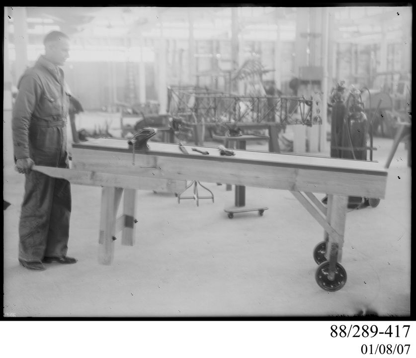 88/289-417 Photographic glass plate negative, man wheeling a portable bench on casters, aircraft workshop, Clyde Engineering Pty Ltd, Australia, 1940. Click to enlarge.