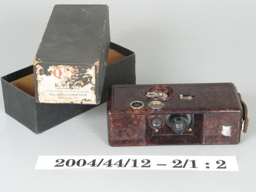 2004/44/12-2 Box camera and packaging, part of collection, 'Kamra', metal / glass/ cardboard, Q R S Devry Corporation, United States of America, 1923-1933