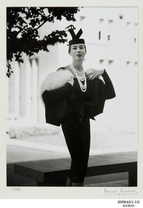 2009/43/1-1/3 Photographic print, black and white, model Diane Masters wears a Hall Ludlow black suit with pill box hat, location Melbourne University, photograph by Bruno Benini, Melbourne, Victoria, Australia, 1956. Click to enlarge.