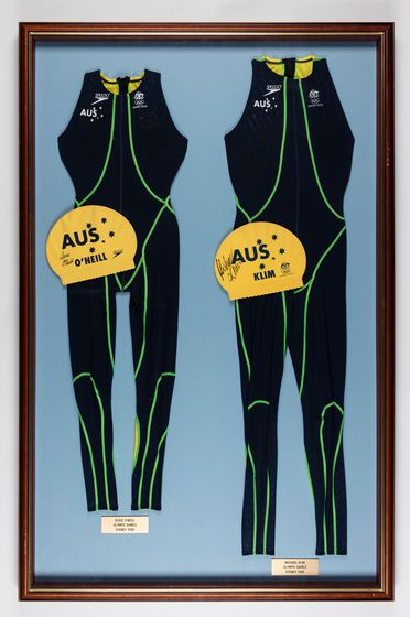 P.13812/12 Swimsuits (2), framed Fastskin sleeveless long body suits and swimming caps (2), 'Australian Swim Team Sydney XXVIII Summer Olympics', Speedo Memorabilia collection, polyester / polymide / rubber / timber / glass, signed by Susie O'Neill and Michael Klim, used by Speedo Australia Pty Ltd,