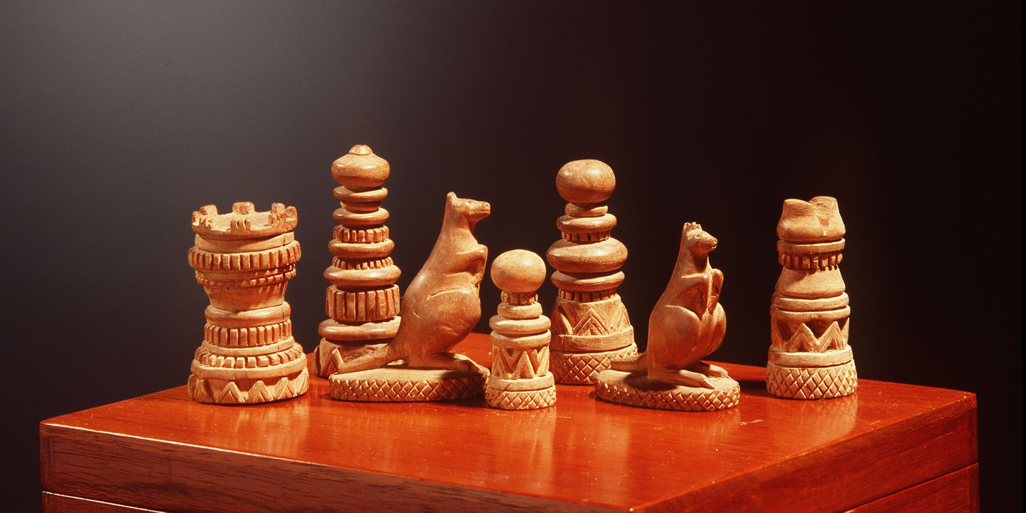 A5589 Sandalwood hand carved chess set. Carved by a W. Aust. prospector who carved for Lord Brassey (Governor of Victoria 1895-1900). Carved with geometric pattern. Knight pieces carved as kangaroos. (LC).. Click to enlarge.