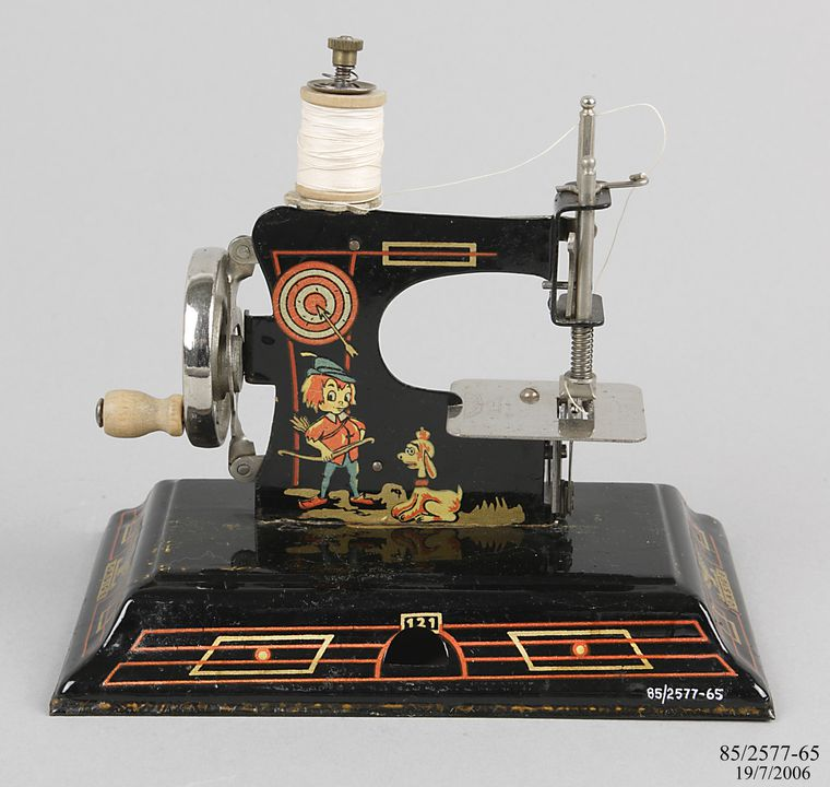 85/2577-65 Casige toy sewing machine, No.121, hand-powered, tin plate, decorated with cartoon decals of William Tell and a fairy, metal / paint, made by Casige, Gevelsberg, British Zone, Germany, 1945-1951. Click to enlarge.