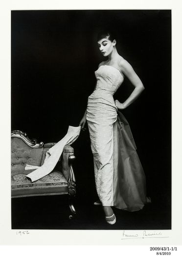 2009/43/1-1/1 Photographic print, black and white, model Pauline Kiernan stands alongside a couch wearing Theo Haskin evening gown, photograph by Bruno Benini, Melbourne, Victoria, Australia, 1956