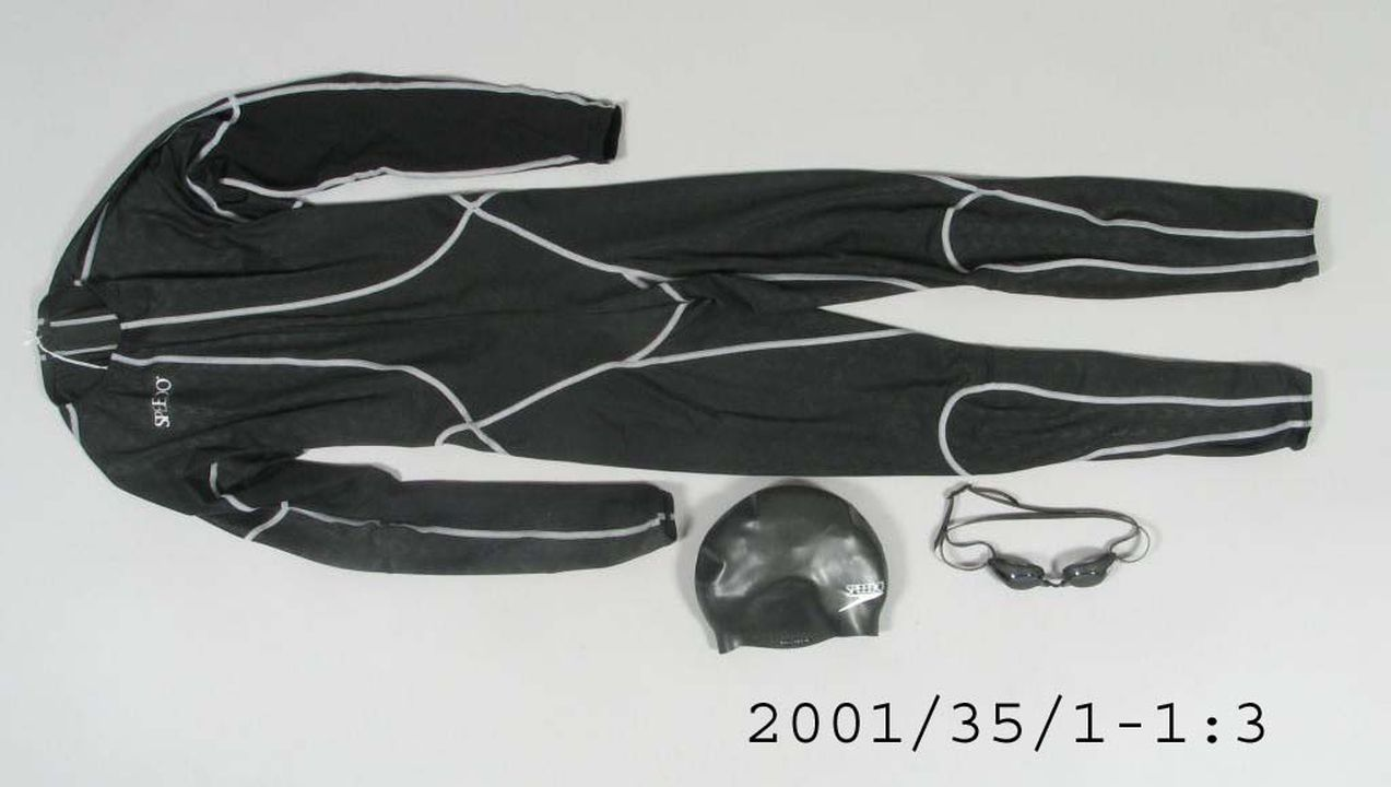 2001/35/1 Swimsuit, mens, 'Fastskin' with goggles, packaging, and swim cap, polyester / elastane, Speedo International, England / Japan / Korea, 2000. Click to enlarge.