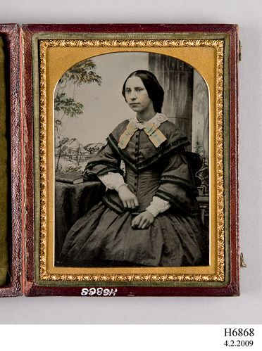 H6868 Photographic positive, ambrotype, hand-tinted, studio portrait of a seated woman, collodion / paint / glass / wood / paper / metal / velvet, photographer unknown, place of production unknown, 1854-1865