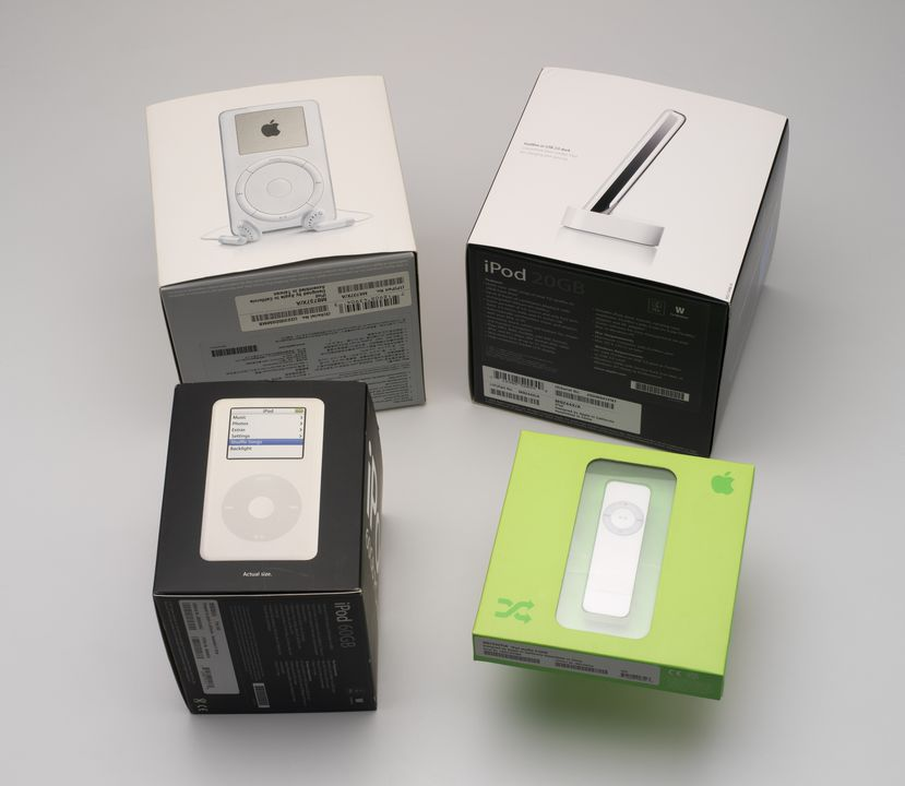 2014/42/1 Digital Media Players (4), iPod 10GB model A1019, iPod 20GB model A1040, iPod 60GB model A1099 & iPod 512MB Shuffle model A1112, original packaging, ear buds, holsters, interconnects, software, warranties and user guides, paper / plastic / metal / electronic components, designed by Jonatha. Click to enlarge.