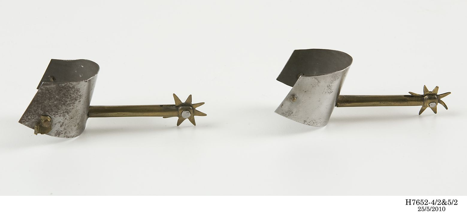 H7652-4 Miniature spur and ankle armour for left foot, part of miniature knight and horse, brass / steel, Paul Hardy, England, c 1890. Click to enlarge.