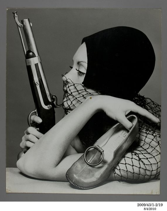 2009/43/1-2/19 Photographic print, fashion, black and white, mounted on card, Moya shoe publicity, model Sandi Mitchell with shoe and gun, photograph by Bruno Benini, Melbourne, Victoria, Australia, 1970. Click to enlarge.
