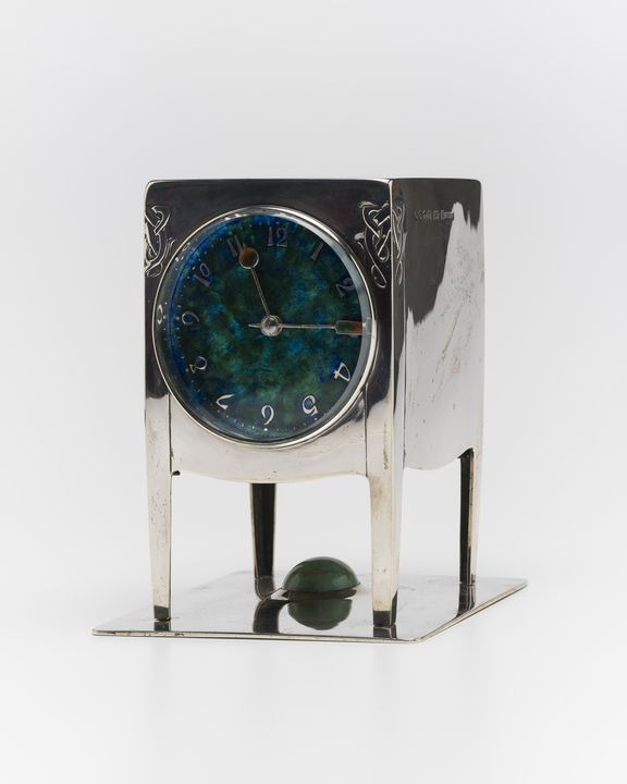 85/85 Clock with key , silver / glass / turquoise / enamel / brass, designed by Archibald Knox, for Liberty & Co, made Birmingham, England, 1902-1903. Click to enlarge.