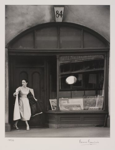 2009/43/1-1/5 Photographic print, black and white, model Helen Homewood wearing Phillipa Gowns dress, standing in a doorway of Melbourne's Eastern Market (now demolished), photograph by Bruno Benini, Melbourne, Victoria, Australia, 1956