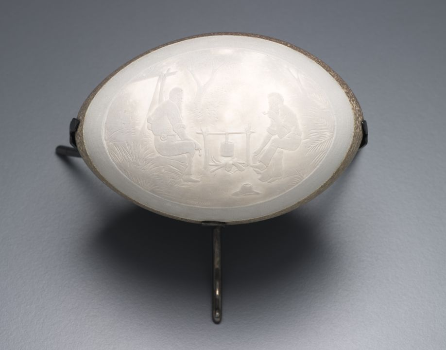 A9407 Emu egg carved in cameo technique and mounted on silver tripod stand, made by Jonaski Takuma, Sydney, Australia, c. 1900. Click to enlarge.
