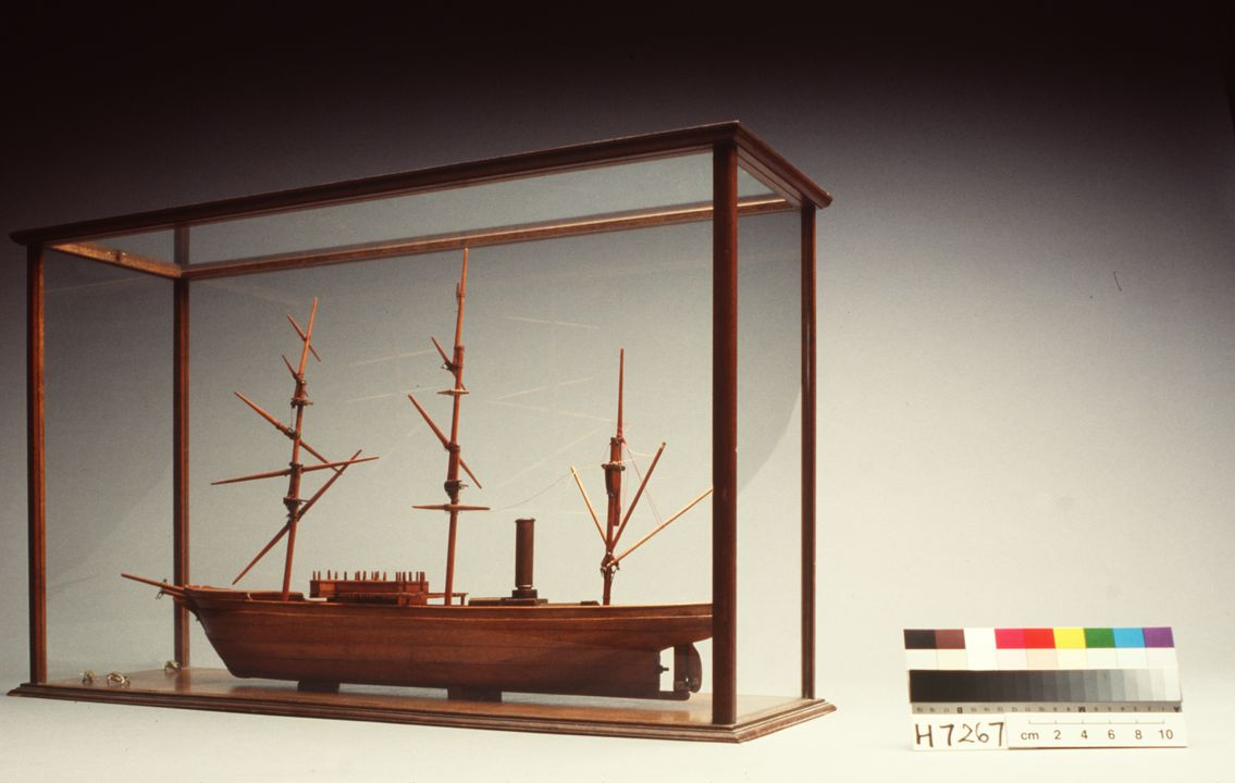 H7267 Ship model (unfinished) with model penguins (3) and display case, HMS 'Discovery', wood / glass / lead / paint, made by Frank Hurley, Australia, unknown date. Click to enlarge.