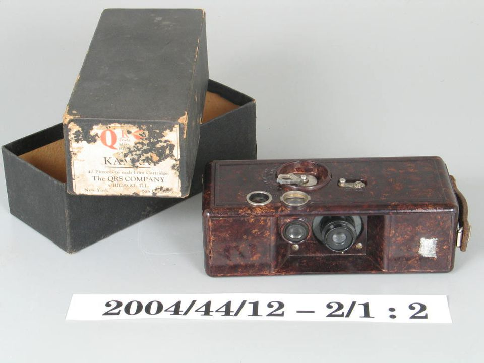 2004/44/12-2 Box camera and packaging, part of collection, 'Kamra', metal / glass/ cardboard, Q R S Devry Corporation, United States of America, 1923-1933. Click to enlarge.