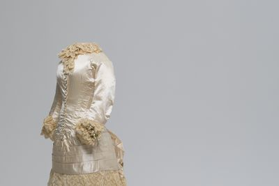A7537 Wedding ensemble in four parts (wedding gown, kid gloves, satin shoes and orange blossom wreath), satin and lace, glass, stiffened muslin, fine cream kid, leather, canvas, wax, paper and cotton, worn by Mary Cameron Murray to her wedding to Varney Parkes, 1883