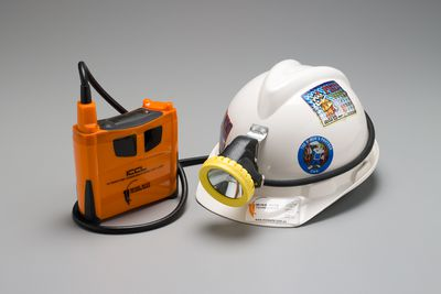 2006/58/1 Miner's cap lamp with base station, 'Integrated Communications Cap Lamp' (ICCL), plastic / metal / cardboard, designed by Tiller + Tiller, made by Mine Site Technologies Pty Ltd, Sydney, New South Wales, Australia, 2004