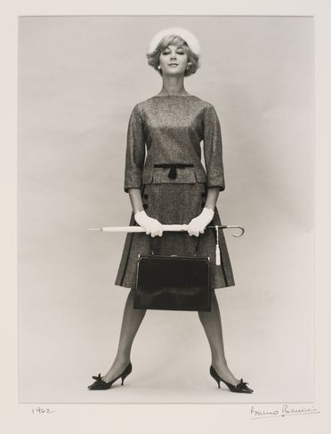 2009/43/1-1/20 Photographic print, black and white, Janice Wakely wears grey flannel Geoff Bade suit, holding an umbrella and bag, studio shot, photograph by Bruno Benini, Melbourne, Victoria, Australia, Melbourne, 1962